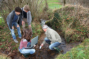 Environmental Management students with tutor taking water samples
